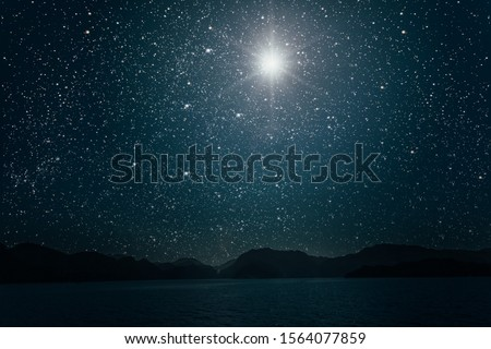 star against a bright night starry sky reflected in the sea. Elements of this image furnished by NASA #1564077859