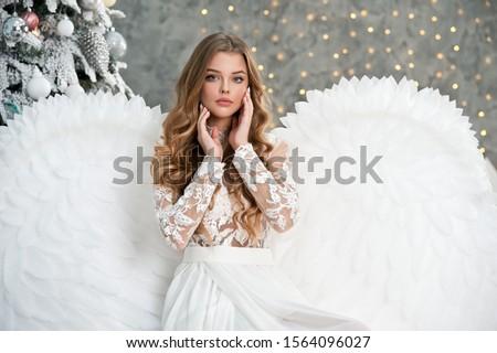 Beautiful young angel woman with big white wings near Christmas tree. Angel. Beautyful girl angel. Christmas. #1564096027