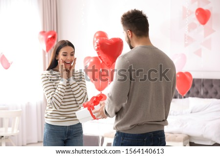 Young man presenting gift to his girlfriend in bedroom decorated with heart shaped balloons. Valentine's day celebration #1564140613