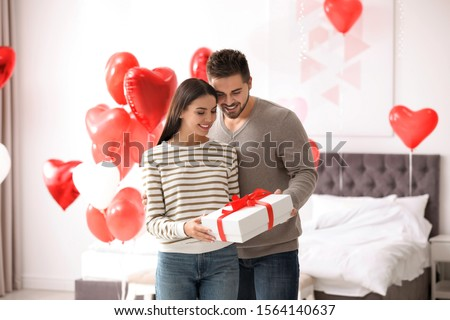 Happy young couple in bedroom decorated with heart shaped balloons. Valentine's day celebration #1564140637