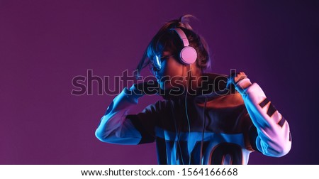 Hipster igen teen pretty fashion girl model wear stylish glasses headphones enjoy listen new cool music mix stand at purple studio background in trendy 80s 90s club blue party light, profile view #1564166668
