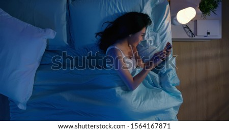 overlooking of asian woman use smartphone on bed at night #1564167871