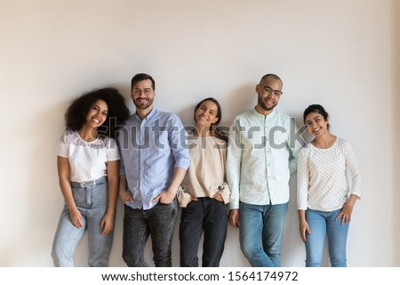 Smiling mixed race young friendly people standing near white wall, portrait. Group of happy multiracial students posing for photo at meeting. Successful diverse colleagues team looking at camera.