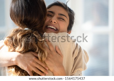 Head shot close up happy mixed race girl cuddling smiling indian female friend. Overjoyed excited best buddies emracing hugging, greeting each other with success, true strong friendship concept. #1564175437