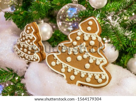 Christmas tree with silver bauble ornaments. Decorated Christmas tree closeup. Balls and illuminated garland with flashlights. New Year baubles macro photo with bokeh. Winter holiday light decoration #1564179304