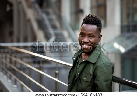 african-american man in stylish jacket on city street in the evening. copy space for text #1564186183