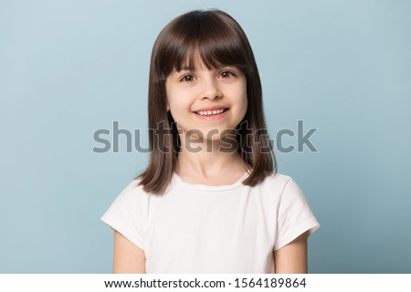 Close up head shot portrait image with smiling little brown-haired girl. Concept happy and beauty kid with good healthy teeth for dental on blue background, six year child looking at camera and posing Royalty-Free Stock Photo #1564189864
