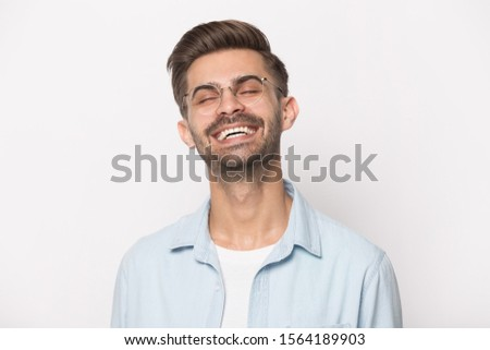 Close up head shot image of happy handsome bearded man loud laughing. Young smiling guy, optimistic businessman laughs widely healthy white teeth for dental on gray background. #1564189903