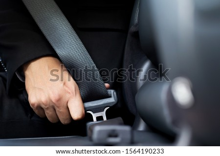 Close Up of people business man hand fastening seat safety belt in car for safety before driving on the road. concept transport travel. soft focus. Royalty-Free Stock Photo #1564190233