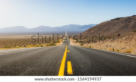 Beautiful panoramic view of a long straight road cutting through a barren scenery of the wild American Southwest with extreme heat haze on a hot and sunny day with blue sky in summer Royalty-Free Stock Photo #1564194937