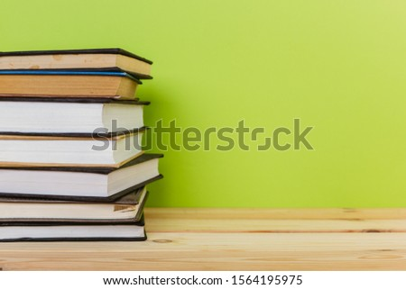 Simple Simple composition of many hardback books, unprocessed books on a wooden table and a green background. back to school. Copy space. Education. #1564195975