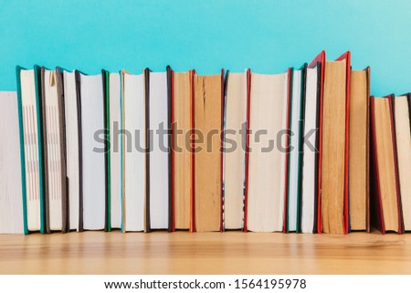 A simple composition of many hardback books, raw books on a wooden table and a bright blue background. Going back to school. Copy space. Education. #1564195978