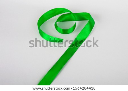 Green ribbon on a gray background. Ribbon for gymnastics. Ribbon for gift. #1564284418