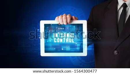 Young business person working on tablet and shows the digital sign: INTERNAL CONTROL #1564300477