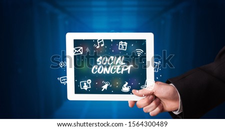 Young business person working on tablet and shows the inscription: SOCIAL CONCEPT #1564300489