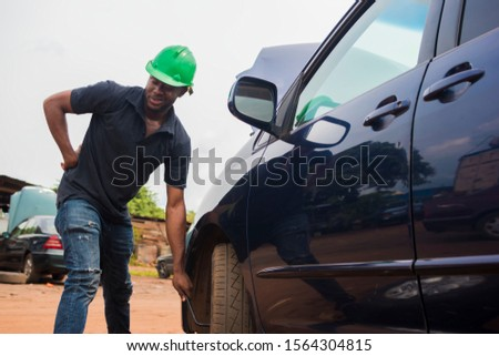 Young black man holding his waist after a stressful moment of changing his tyre #1564304815