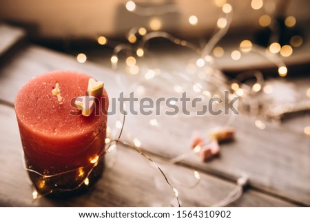 Romantic candle on a bokeh background. On top of the candle are two marshmallow hearts. New Year decorations and decorations #1564310902