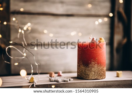Romantic candle on a bokeh background. On top of the candle are two marshmallow hearts. New Year decorations and decorations #1564310905