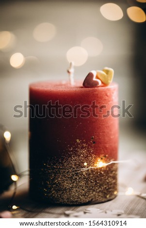 Romantic candle on a bokeh background. On top of the candle are two marshmallow hearts. New Year decorations and decorations #1564310914