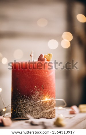 Romantic candle on a bokeh background. On top of the candle are two marshmallow hearts. New Year decorations and decorations #1564310917