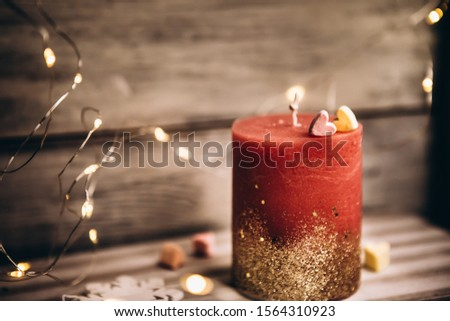 Romantic candle on a bokeh background. On top of the candle are two marshmallow hearts. New Year decorations and decorations #1564310923