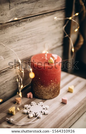 Romantic candle on a bokeh background. On top of the candle are two marshmallow hearts. New Year decorations and decorations #1564310926