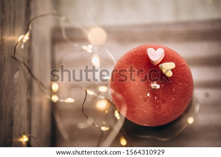 Romantic candle on a bokeh background. On top of the candle are two marshmallow hearts. New Year decorations and decorations #1564310929