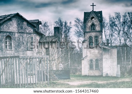 Old Catholic Church in the evening fog. The building of medieval Europe in dark colors. Mystical sky with storm clouds..