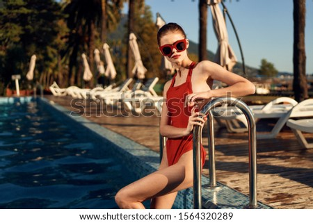 Strong woman red swimsuit in summer resort luxury resort pool #1564320289