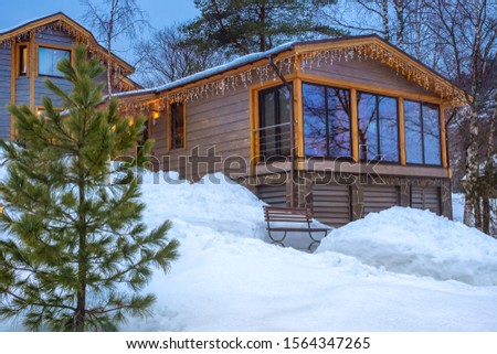 The wooden cottage is decorated with garlands. Winter in the countryside. Winter holidays in cottages. Cozy area around the houses. Home for a large family. Rent cottages. Apartment. #1564347265