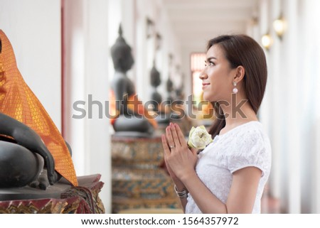 Religious Asian buddhist woman praying. Female buddhist disciple meditating, chanting mantra with prayer hand to the statue of lord Buddha in temple hall; asian young adult woman model #1564357972
