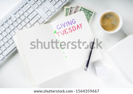 Notepad for To-Do list Giving Tuesday. White paper ready to write notes to various helping on Tuesday. International Charity Aid Day, giving hashtag activity. On a white desktop flatlay copy space #1564359667