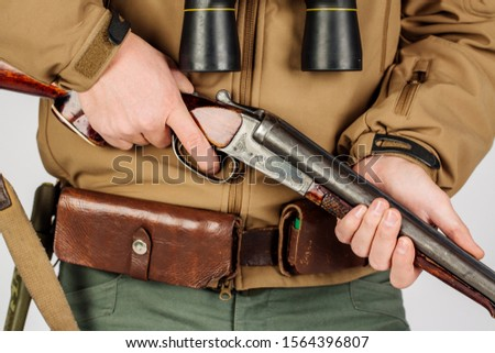 Men's hands with a hunting gun reload the cartridge #1564396807