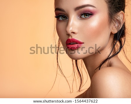 Beautiful white girl with red lips looks to the camera. Stunning brunette girl. Closeup face of young beautiful woman with a healthy clean skin. Pretty woman with bright  makeup of eyes. #1564437622