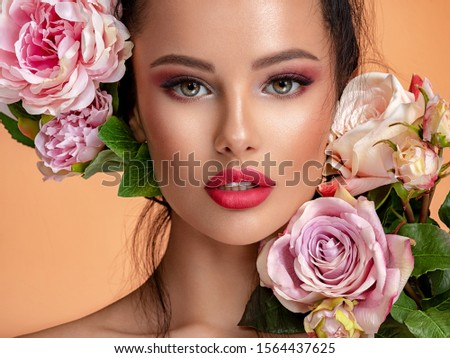 Beautiful white girl with flowers. Stunning brunette girl with big bouquet flowers of roses. Closeup face of young beautiful woman with a healthy clean skin. Pretty woman with bright makeup #1564437625