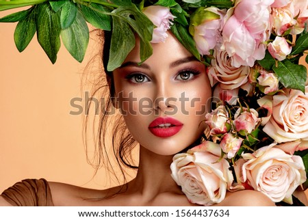 Beautiful white girl with flowers. Stunning brunette girl with big bouquet flowers of roses. Closeup face of young beautiful woman with a healthy clean skin. Pretty woman with bright makeup #1564437634