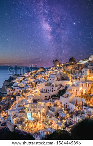 Oia village in sunset light with stars and milky way, Santorini, Greece. Amazing summer vacation landscape, white architecture and evening lights. Famous travel destination, urban travel background #1564445896