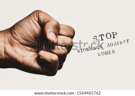 closeup of a man with his fist threateningly closed and the text stop violence against women against an off-white background #1564465762