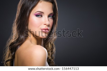 Portrait of beautiful girl with bright pink make-up on grey background. Concept of beauty and fashion #156447113