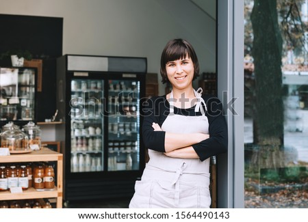 Portrait of owner of sustainable small local business. Shopkeeper of zero waste shop standing on interior background of shop. Smiling young woman in apron welcoming at entrance of plastic free store #1564490143