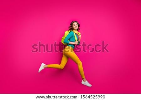 Full length body size side profile photo of cheerful casual cute curly wavy pretty girlfriend wearing white sneakers yellow pants trousers smiling toothily isolated fuchsia vibrant color background