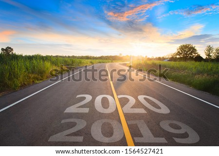 The word 2020 written on highway road in the middle of empty asphalt road at golden sunset and beautiful blue sky. Concept for new year 2020. #1564527421