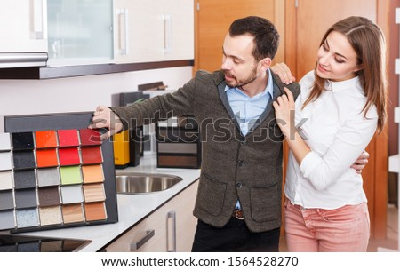 Married couple looking for stylish materials for kitchen furnishing in salon #1564528270