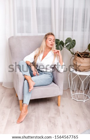 Cute blonde sits beautifully in her chair, home comfort and comfort #1564567765