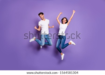 Full length body size photo of cheerful excited positive ecstatic jumping people in jeans denim white t-shit footwear expressing emotions isolated pastel violet color background #1564581304