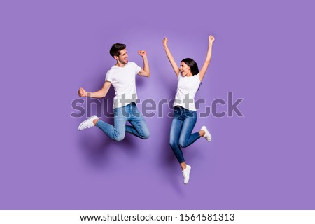 Full length body size photo of cheerful excited ecstatic positive crazy people in white footwear t-shirt jeans denim brown hair jumping screaming yeah isolated pastel color violet background #1564581313