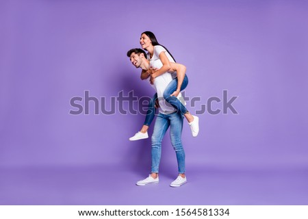 Side profile full length body size photo of cheerful positive cute piggyback couple in t-shirt denim with man carrying woman smile toothy isolated pastel violet color background #1564581334