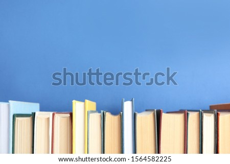 Collection of old books on blue background. Space for text #1564582225
