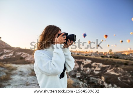 Travel photographer wearing white sweater taking a picture of balloons in Cappadocia. Travel photographer in Turkey