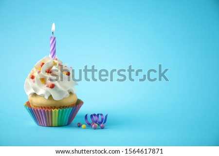 Delicious birthday cupcake with candle on light blue background. Space for text #1564617871